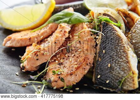Teppanyaki Style Seafood - Grilled Mixed Seafood with Soy Sauce and Vegetables. Japanese Teppanyaki Salmon Steak, Shrimp, Scallop and Fish Fillet garnished with lemon and green salad