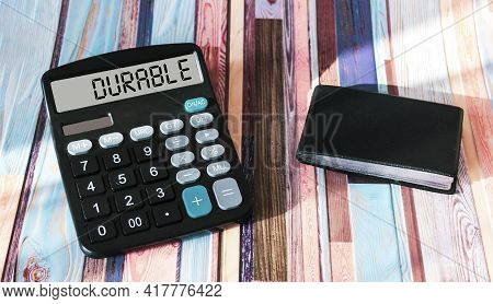 The Text Is Durable On The Display Of A Calculator With An Office Card Holder On A Striped Colored B