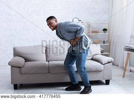 Black Man Having Stomachache Suffering From Abdominal Spasm At Home