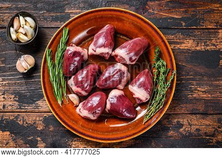 Fresh Raw Turkey Hearts Offal Giblets With Thyme And Rosemary. Dark Wooden Background. Top View