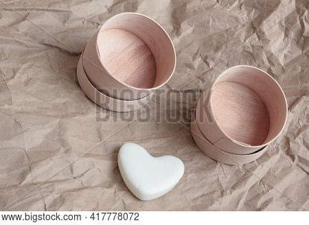 On A Paper Background There Are Two Empty Round Birch Bark Boxes,  Dry Shampoo In The Form Of A Whit