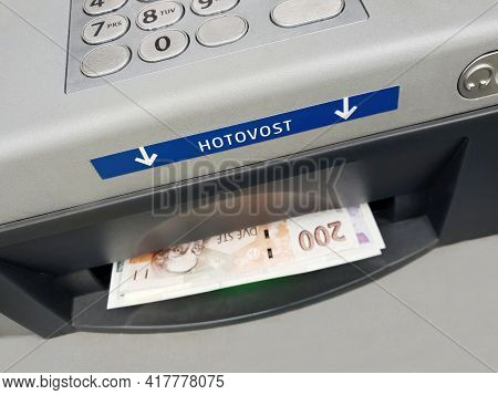 Prague, Czech Republic - April 15, 2021: Withdrawing Money From Atm Of Ceska Sporitelna Bank. Ceska