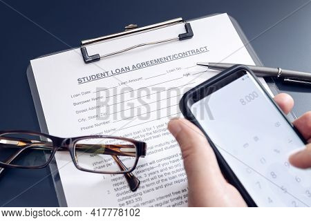 Blank Student Loan Application On Table And Hand Holding A Smartphone With Calculator App. Education