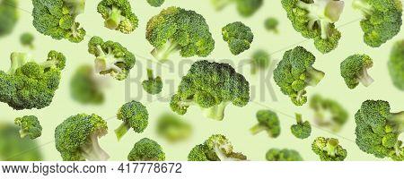 Flying Fresh Raw Green Broccoli On Light Green Background. Creative Food Concept. Healthy Diet Vegan