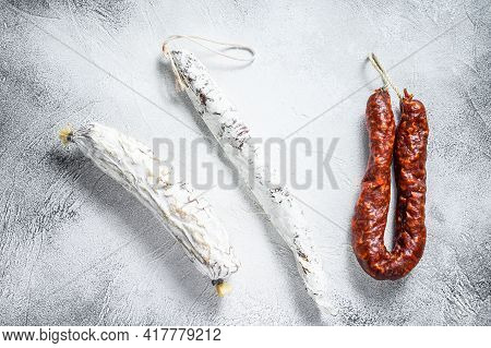 Spanish Salami, Fuet And Chorizo Sausages On A Kitchen Table. White Background. Top View