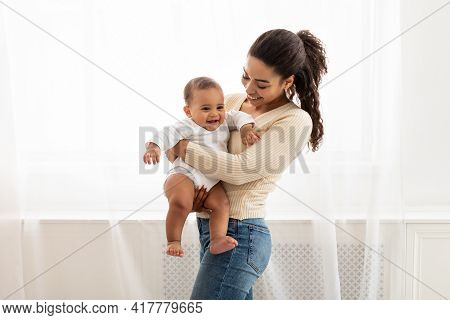 Joyful Black Mommy Carrying Baby In Arms Standing At Home