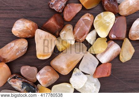 Red Silk Jade Jewel Stones Heap Up Stones Texture On Brown Varnished Wood Background