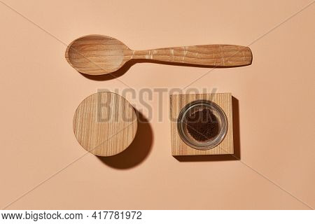 Organic Coffee Scrub Next To Wooden Spoon On Light Orange Background, Flat Lay, Top View. Beauty Tre