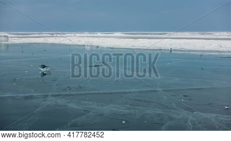 Transparent Pieces Of Ice Are Scattered Over The Frozen Lake. Reflection On The Surface, Cracks In T