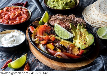Close Up Of A Cast Iron Skillet Filled With Fajita Ingredients And Surrounded By More Toppings And T