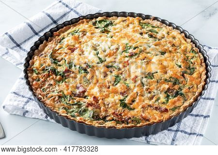 Spinach And Bacon Quiche In A Tart Pan On A Kitchen Towel Taken From Above.