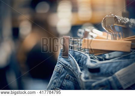 Jeans On The Hanger In The Store. Clothes On Hangers In Shop For Sale. Blur Background. Fashionable