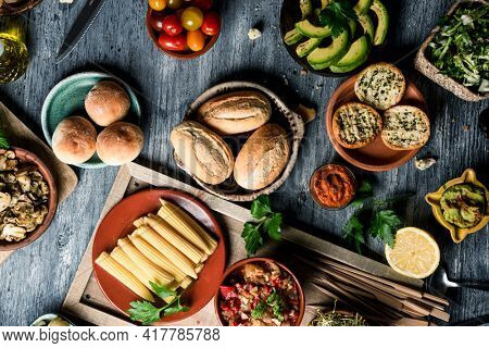 high angle view some different vegan snacks, side dishes, dips such as guacamole, and some other ingredients to prepare vegan sandwiches, on a gray rustic wooden table