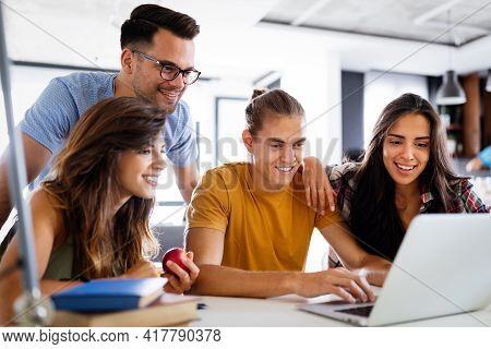 Multiracial Young People Enjoying Group Study At Table.