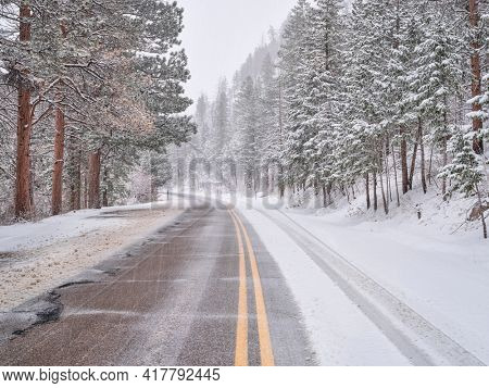 winter travel in Colorado Rocky Mountains - highway in Poudre Canyon in a heavy early spring snowstorm