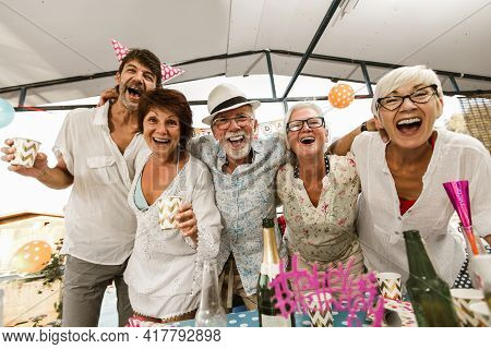 Senior People Celebrating Birthday In The Cottage On The River Having Fun.