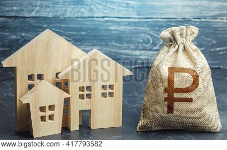 Russian Ruble Money Bag And Figurines Of Residential Buildings. Property Tax. Increase Investment At