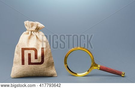 Israeli Shekel Money Bag And Magnifying Glass. Financial Audit. Origin Of Capital And Legality Of Fu
