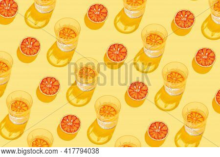 Creative Pattern Made With Sliced Grapefruit, Blood Orange And Glass With Lemonade Or Water On Yello
