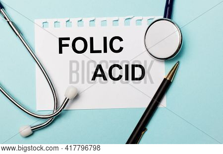 On A Light Blue Background, A Stethoscope, A Pen And A Sheet Of Paper With The Inscription Folic Aci