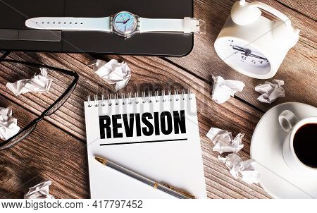 There Is A Cup Of Coffee On A Wooden Table, A Clock, Glasses And A Notebook With The Word Revision.