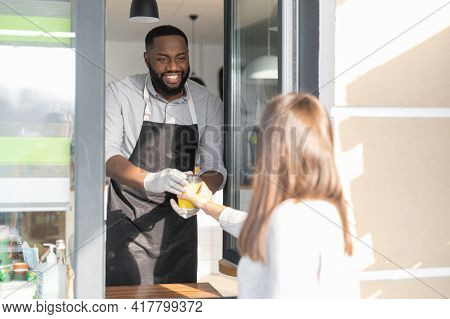 A Cheerful And Smiling African-american Waiter Is Serving Female Customer, A Multiracial Cafe Manage