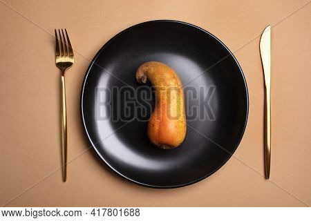 Top View Of Ugly Bent Ripe Pear Lies On Round Black Plate With Golden Cutlery On Beige Background.