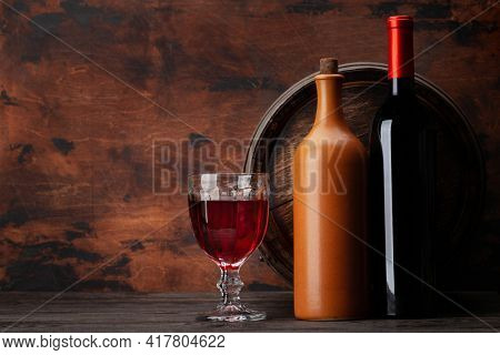 Wine bottles, glass of red wine and old wooden barrel. With copy space