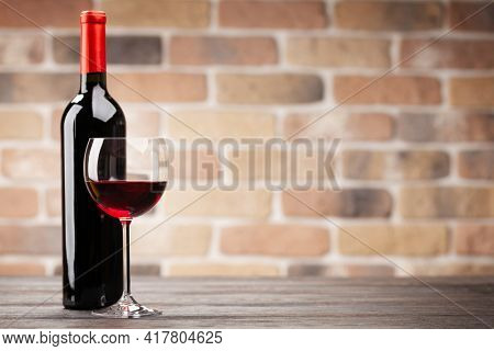 Wine bottle and glass of red wine on wooden table. With copy space