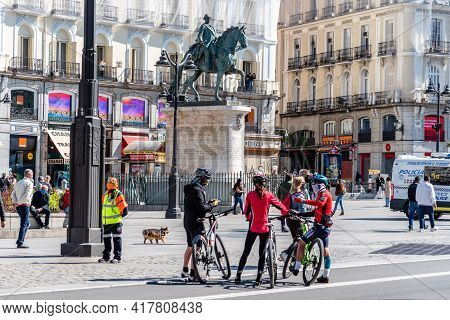 Madrid, Spain - April, 18 2021: Cyclists Standing In Puerta Del Sol Square In Central Madrid. Street