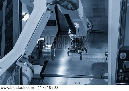 The Robotic Arm Gripping The Metal Part From Cnc Lathe Machine. The Hi-technology Material Handling