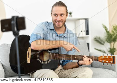 A Hipster Guy Is Plays Guitar And Records Himself On A Video Using Smartphone. Online Teacher Guitar