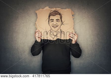 Anonymous Man Covers His Head With A Fake Mask, Hiding Emotions Behind A Torn Cardboard Sheet With A