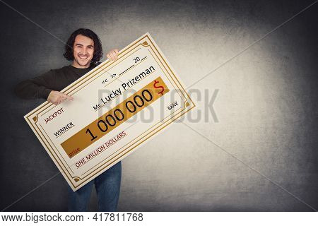 Excited Man Holding A Lottery Winner Bank Check. Happy Guy Jackpot Winning One Million Dollars Prize