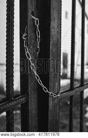 Steel Chain Hanging On The Gate. The Gate Is Chained. Black And White Photo