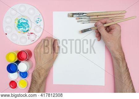 The Artist Paints With Acrylics. Holds A Brush In His Hand. Mockup Flat Lay. Artists Hand Over A Bla