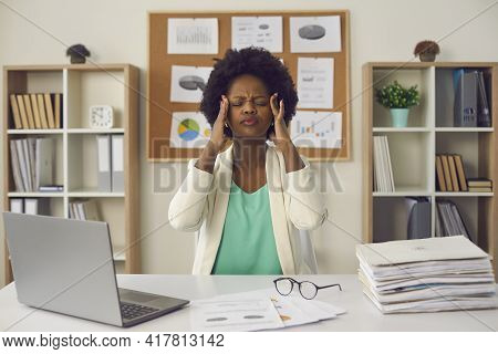 African American Businesswoman Rubbing Temples Sitting At Office Desk Portrait