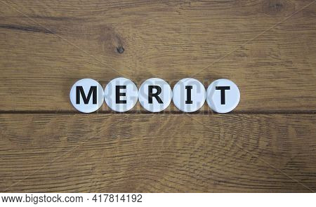 Merit Symbol. Wooden White Circles With The Word 'merit'. Beautiful Wooden Background, Copy Space. B