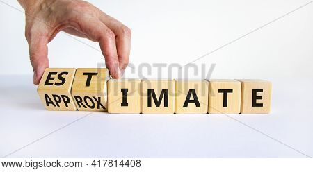 Estimate Or Approximate Symbol. Businessman Turns Wooden Cubes And Changes The Word 'approximate' To