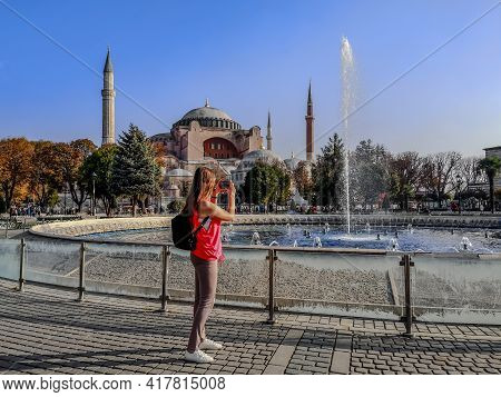Tourist Girl Shoots A Fountain On A Smartphone In Sultanahmet Square In Front Of Hagia Sophia In Ist