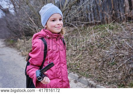 A Little Girl, A Blogger With A Camera In Her Hand, Is Walking Down The Street. Against The Backgrou