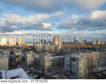 Winter City View In Eastern Europe. Rooftops Of Multistory Buildings Covered With Melting Snow. Aeri