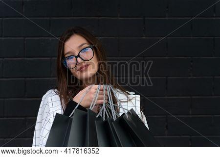 Stylish Girl Student In Glasses Holds Black Shopping Bags Against Black Wall. Black Friday.