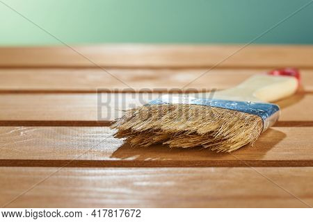 Varnishing Natural Wood With Paint Brush. Paint Brush On A Wooden Surface.