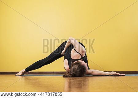 A Woman In Black Sportswear Is Engaged In Yoga, Performs An Intense Twist Of The Spine In The Studio