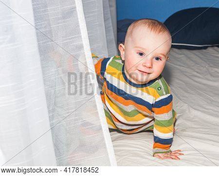 Portrait Of An Eight Month Old Baby Boy In Striped Clothes