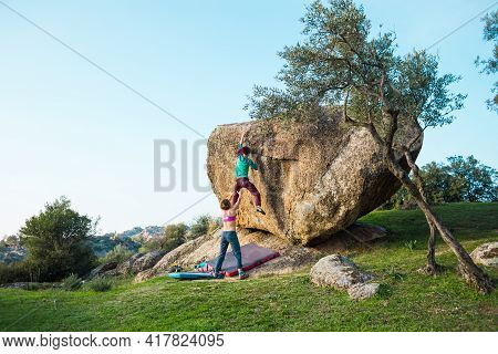 Strong Girl Climb Bouldering With Friends In Nature. Rock Climbing In Nature As Fitness And Sports.