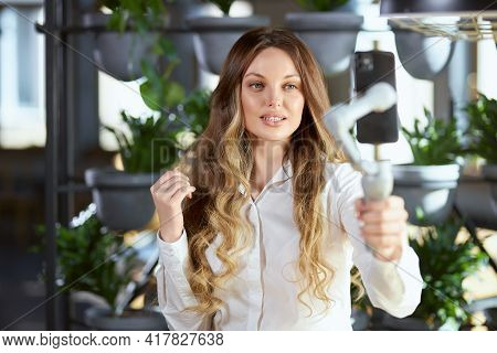Front View Of Attractive Woman With Long Hair In White Shirt Holding Selfie Stick And Communicating