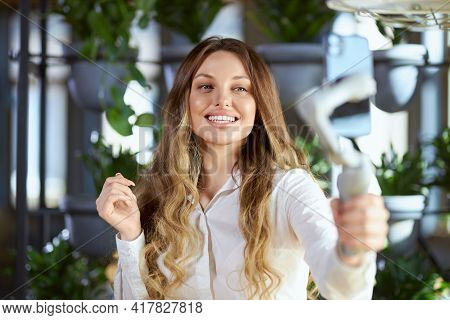 Front View Portrait Of Smiling Attractive Young Woman In White Shirt Holding Selfie Stick And Commun