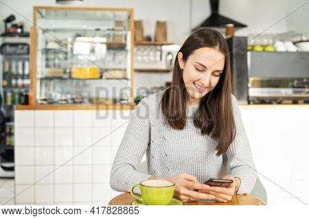 Smiling Young Brunette Woman Enjoys A Morning Coffee Sitting In The Cozy Cafe And Chatting On The Sm
